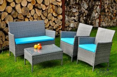 Meble z technorattanu z niebieskimi poduszkami w ogrodzie z drewutnią