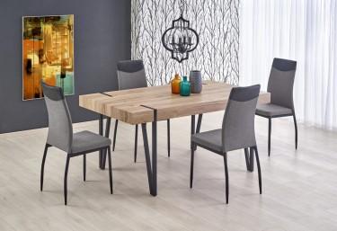 Stół na metalowych nogach u boku krzeseł tapicerowanych tkaniną z modnym obrazem na szarej ścianie