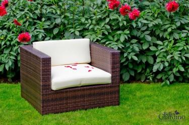 Fotel z technorattanu z miękkimi poduszkami w ogrodowej scenerii z kwitnącymi kwiatami