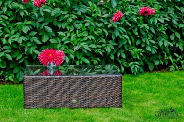 Stolik z rattanu syntetycznego ze szklanym blatem w ogrodzie z kwitnącą roślinnością