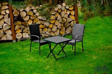 Czarne meble do użytku zewnętrznego ustawione przy składowisku drewna w przydomowym ogrodzie