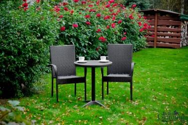 Zestaw mebli dla 2 osób w ogrodzie z kwitnącymi kwiatami i składowiskiem drewna opałowego