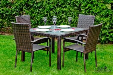 Zestaw mebli dla czterech osób ze stołem i szklaną nakładką w przydomowym ogrodzie