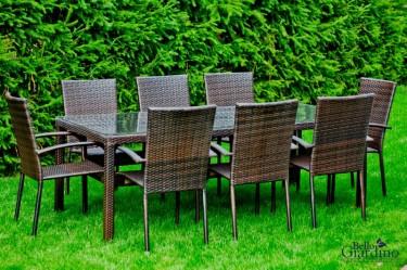 8-osobowy zestaw mebli obiadowych z technorattanu w ogrodzie z bujną roślinnością