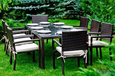 Duży zestaw mebli stołowych dla 8 osób w ogrodzie z bujną roślinnością