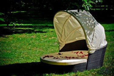 Łóżko z miękkim materacem i baldachimem w przydomowym ogrodzie