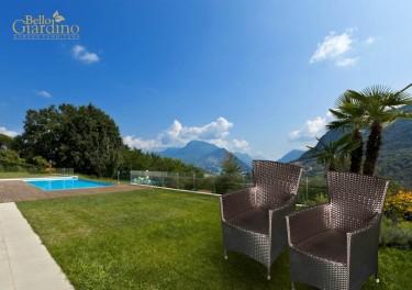 Brązowe fotele z technorattanu w ekskluzywnym ogrodzie z basenem na tle gór