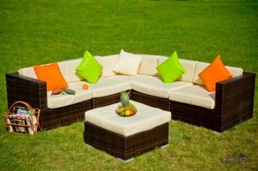Narożna sofa i pufa z miękkimi poduszkami w przydomowym ogrodzie