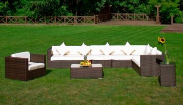 Zestaw mebli z technorattanu ze stolikiem kawowym w dużym ogrodzie z drewnianym ogrodzeniem
