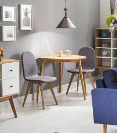 Drewniany stół z półokrągłym blatem na trzech nogach i szare tapicerowane krzesła na drewnianej podstawie