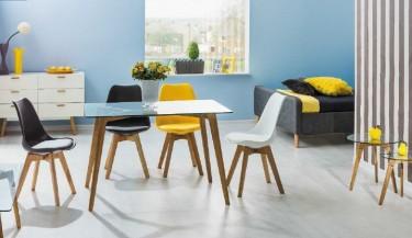 Kolorowe krzesła z ekoskóry bez podłokietników oraz stół ze szklanym blatem i drewnianymi nogami