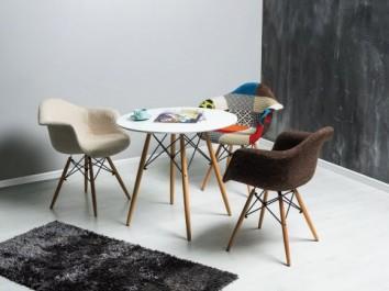 Stolik w stylu skandynawskim z okrągłym blatem i patchworkowe krzesła na drewnianych nogach z obszernym siedziskiem