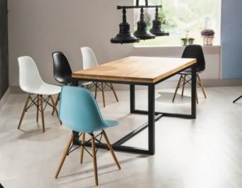 Stół z drewnianym blatem na metalowej podstawie i kolorowe krzesła bez podłokietników