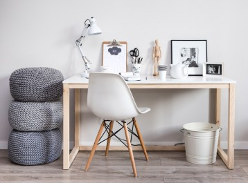 Biurko z prostokątnym blatem na drewnianej podstawie oraz białe krzesło w stylu skandynawskim