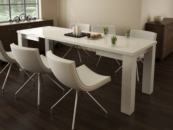 Rozkładany biały stół w wysokim połysku i skórzane krzesła na metalowych nóżkach w jadalni z ciemną podłogą