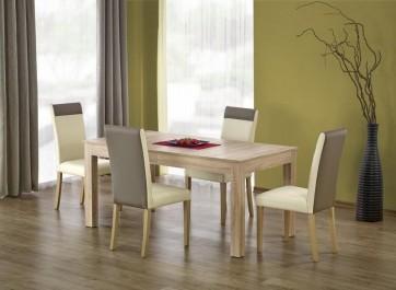 Zestaw mebli w postaci rozkładanego stołu i skórzanych krzeseł w jadalni z drewnianą podłogą i zielonymi ścianami