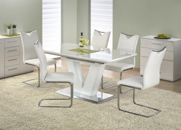 Rozkładany stół z lakierowanym blatem i krzesła w jadalni z dużym dywanem i dwoma białymi komodami