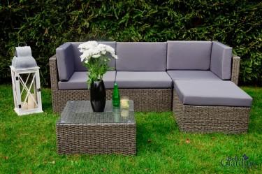Zestaw mebli modułowych w ogrodzie z sofą narożną i stolikiem ze szklanym blatem