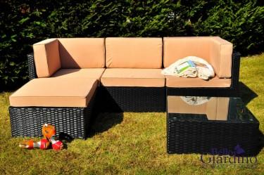 Narożna sofa z poduszkami i stolik ze szklaną nakładką w ogrodzie