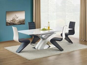 Lakierowany stół z elementami ze stali nierdzewnej w towarzystwie czarnych krzeseł z ekoskóry