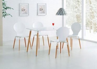 Białe krzesła na drewnianych nogach i stół z lakierowanym blatem w stylu skandynawskim