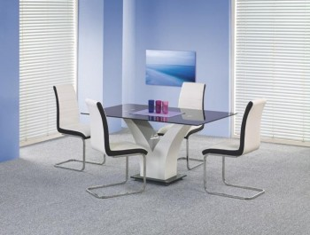 Nierozkładany stół na jednej nodze z blatem szklanym i dwukolorowe krzesła na płozach