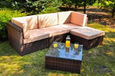 Sofa narożna z miękkimi poduchami oraz stolik ze szklanym blatem w dużym ogrodzie