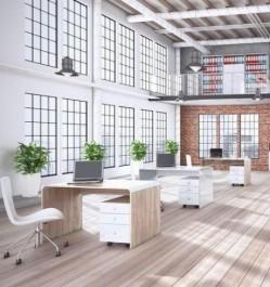 Meble biurowe w nowoczesnym wnętrzu pracowniczym z dużą ilością okien i ceglaną ścianą