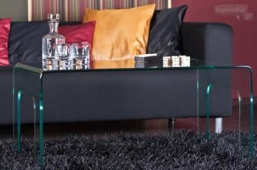 Ława z bezbarwnego szkła giętego w towarzystwie czarnej sofy ze skóry