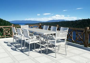Białe krzesła kawiarniane z perforowanym siedziskiem uzupełnieniem białych stolików na tarasie z widokiem na góry
