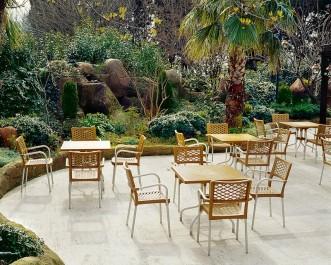 Kawiarniane krzesła z tworzywa sztucznego z podłokietnikami i brązowe stoliki na metalowej podstawie