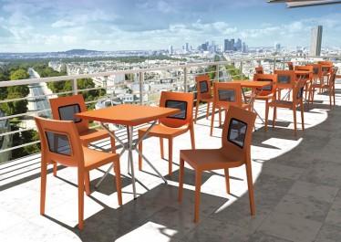 Designerskie krzesła bez podłokietników i stoły na metalowej podstawie na tarasie z widokiem na panoramę miasta