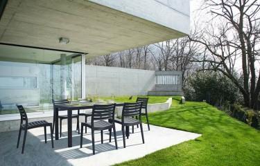 Czarne krzesła ogrodowe bez podłokietników z dużym stołem obiadowym na czterech nogach