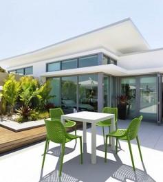 Sztaplowane zielone krzesła bez podłokietników i minimalistyczny stół uzupełnieniem tarasu z bujną roślinnością