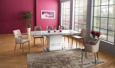 Rozkładany stół z blatem w dekorze marmur i krzesła tapicerowane beżową tkaniną