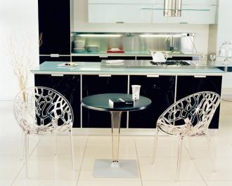 Przezroczyste krzesła z ażurowym siedziskiem i okrągły stół z czarnym blatem na jednej nodze
