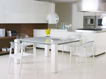 Białe krzesła kuchenne z przezroczystym oparciem i nierozkładany stół jako uzupełnienie przestronnej jadalni