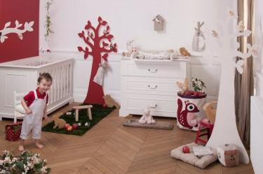Pokój dziecięcy z biało - czerwonymi ścianami wyposażony w łóżeczko i komodę z przewijakiem
