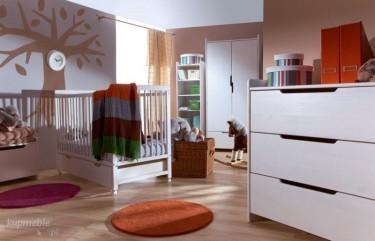 Drewniane łóżeczko na kółkach w dużym pokoju dziecięcym z drewnopodobną podłogą