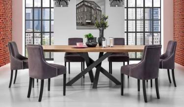 Duży nierozkładany stół z drewnianym blatem w stylu industrialnym w towarzystwie tapicerowanych krzeseł