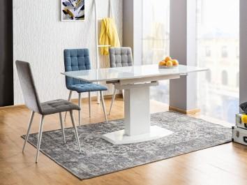 Kolorowe pikowane krzesła na białych nóżkach i biały rozkładany stół o połyskującej powierzchni