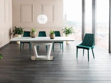 Biały stół z rozkładanym blatem na podstawie z tworzywa sztucznego i turkusowe pikowane krzesła