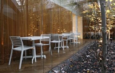 Białe krzesła do kawiarni bez podłokietników oraz stoliki z kwadratowym blatem