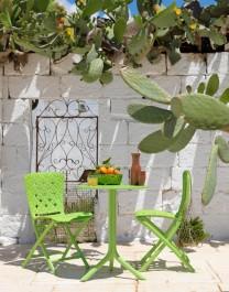 Zielony stół z okrągłym blatem oraz składane krzesła bez podłokietników z ozdobną fakturą