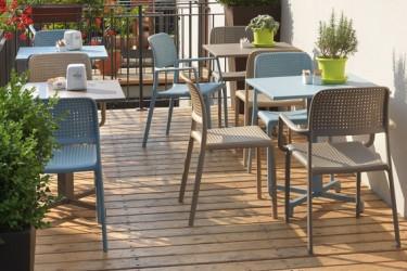Krzesła z tworzywa sztucznego z perforowanymi siedziskami oraz stoliki z kwadratowym blatem
