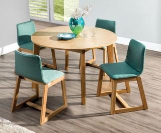 Rozkładany okrągły stół z fornirowanym blatem i zielone tapicerowane krzesła na drewnianych płozach