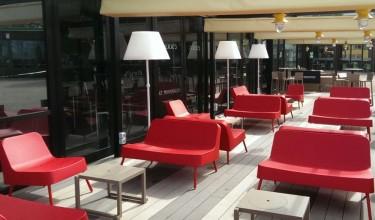 Stołki barowe z podnóżkami oraz czerwone sofy i fotele na aluminiowych nóżkach