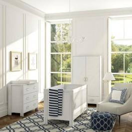 Białe łóżeczko dziecięce z funkcją tapczanika oraz szafa ubraniowa i komoda z trzema szufladami