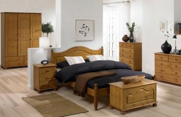 Zestaw drewnianych mebli do nowoczesnej oraz tradycyjnej sypialni na tle białych ścian i jasnej podłogi