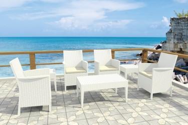 Wypoczynkowe fotele ogrodowe z wysokimi podłokietnikami oraz stoliki kawowe i prostokątna ława